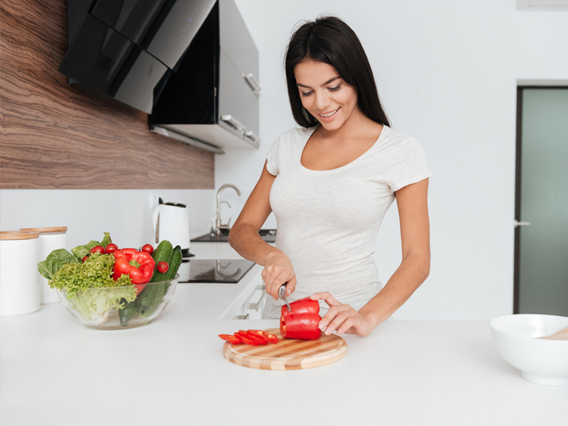graphicstock-photo-of-young-woman-cooking-in-the-kitchen-looking-at-products_rU8_bKm_ne